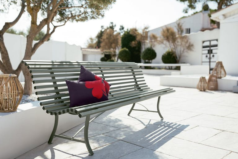 Fermob Louisiane contemporary metal park bench sitting on pavers in residential garden