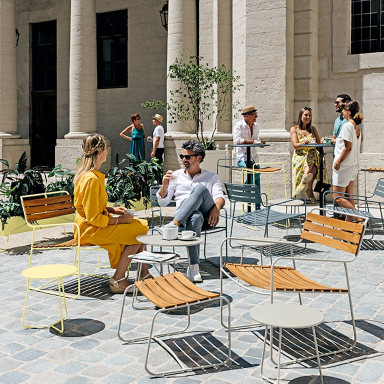 Group of people lounging on Fermob metal outdoor furniture in Frosted Lemon, Clay Grey, and Storm Grey colours
