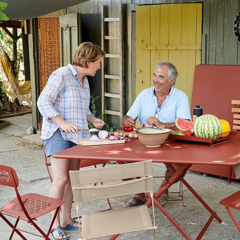 Couple prepare vegetables on an outdoor table