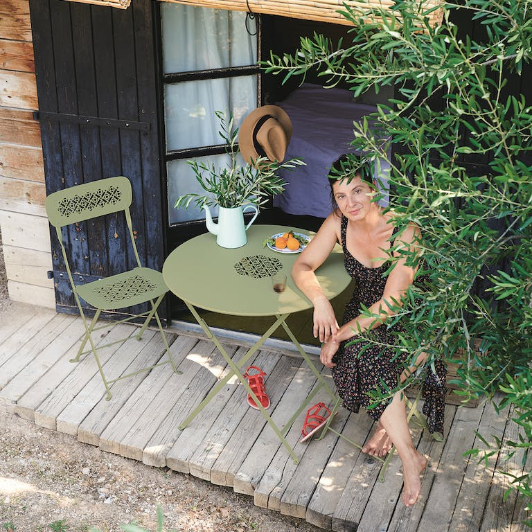 Woman sits at round cafe setting by olive tree