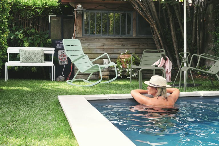 Fermob Luxembourg rocking chair sits on grass behind woman in pool