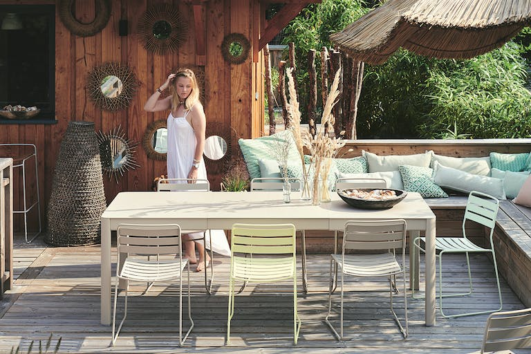 Woman stands behind Fermob extending outdoor dining table in Clay Grey colour