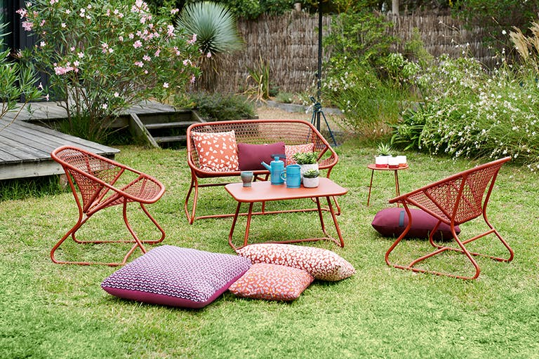 Fermob Sixties outdoor casual setting in Red Ochre on grass in a garden
