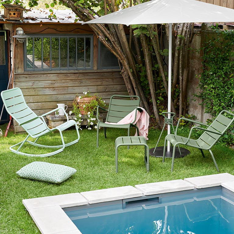 Fermob Luxembourg outdoor furniture in relaxed backyard by pool