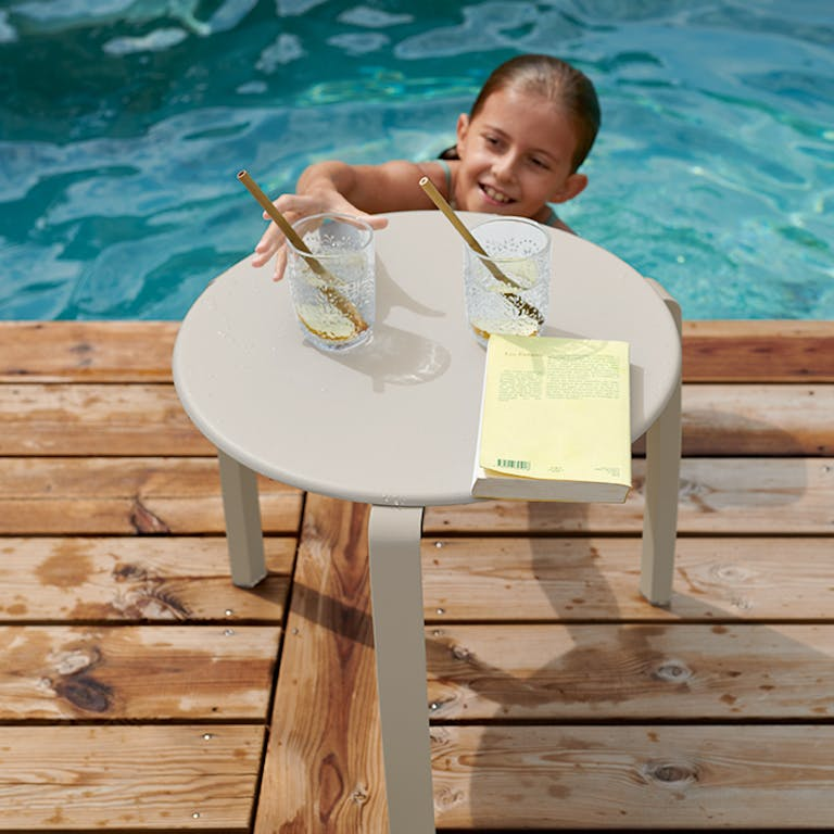 Child reaches from pool for drink off Alize side table in Clay Grey