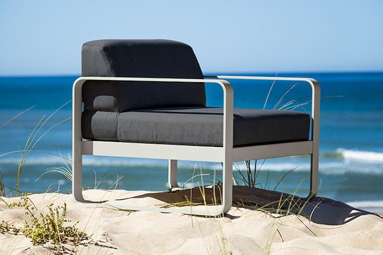 Fermob Bellevie sofa armchair sitting on a sand dune at beach