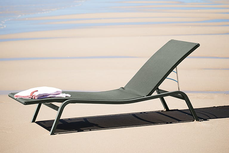 Fermob Alize sunlounger on the beach in the sun