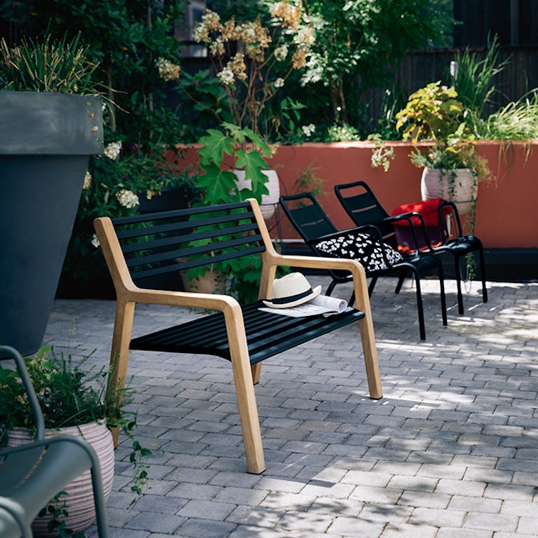 Somerset garden bench with metal slats and wooden ends in hotel courtyard