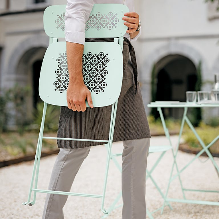 Waiter carries a folded cafe chair at Grand Hotel Dieu Lyon