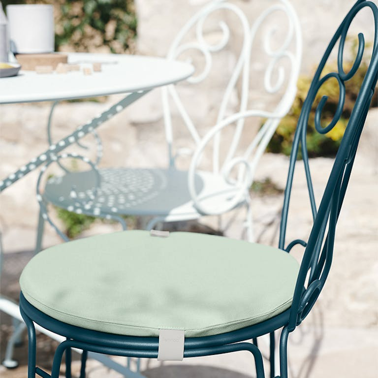 Close up of Fermob Montmartre metal chair in Acapulco Blue with seat cushion