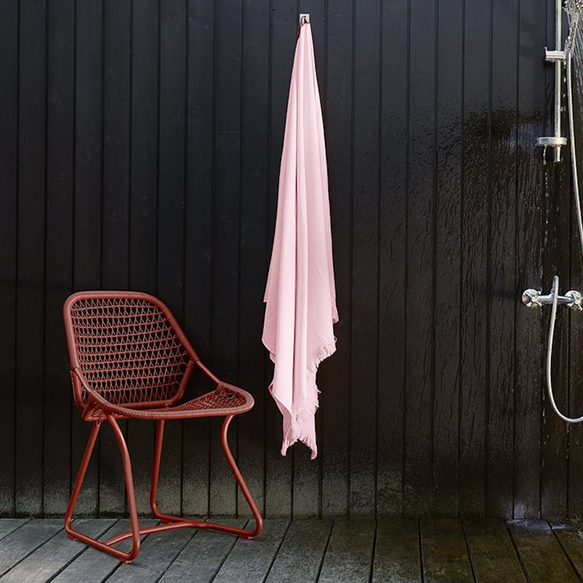 Fermob outdoor dining chair from the Sixties collection in Red Ochre in front of black wall