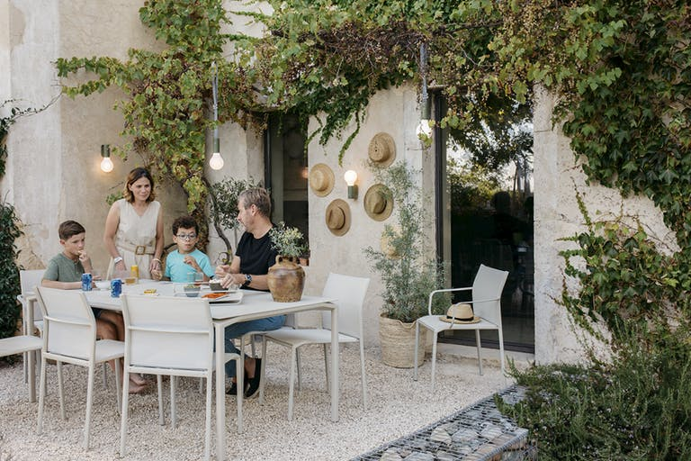 Family dining outdoors with Fermob Cadiz and Calvi collections