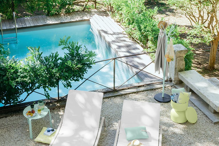 Man stands next to pool and two sun loungers