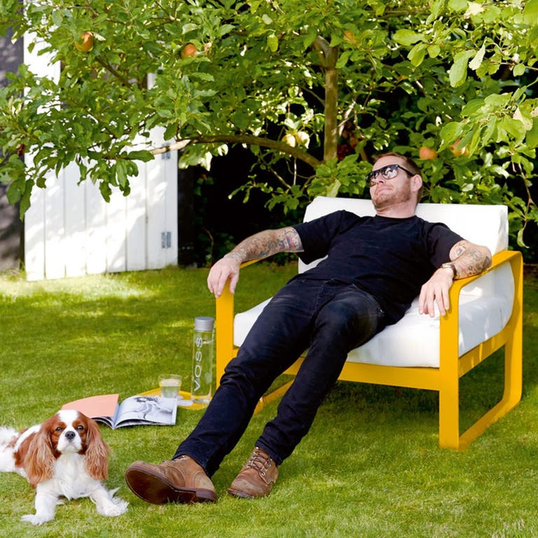 Man relaxes on Honey coloured Fermob Bellevie sofa armchair in a garden with dog