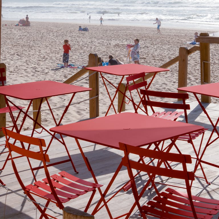 Red cafe folding furniture at a beach