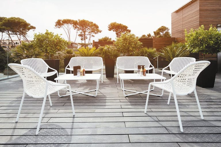 Fermob Croisette white outdoor chairs, sofas and low tables at a bar terrace
