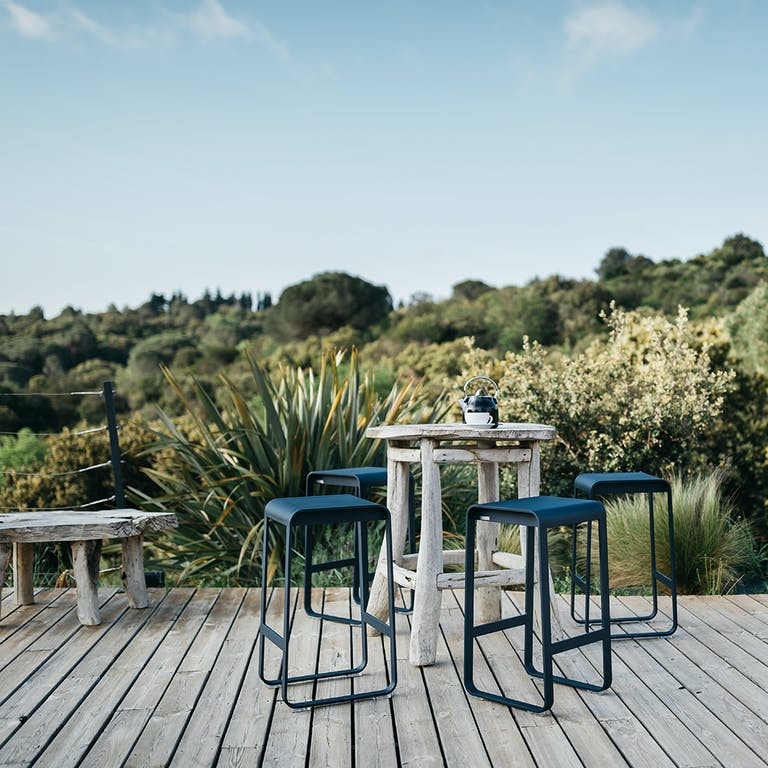 Four Fermob Bellevie contemporary bar stools sit around a rustic table on a deck overlooking bush